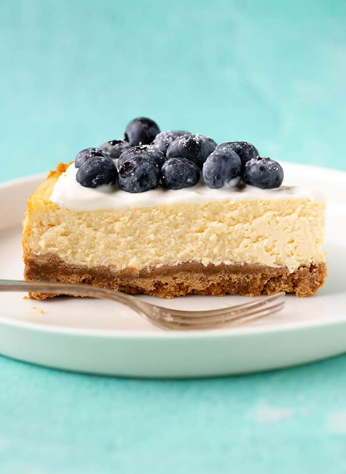 Side view of a slice of Lemon Cheesecake on a white plate with a fork