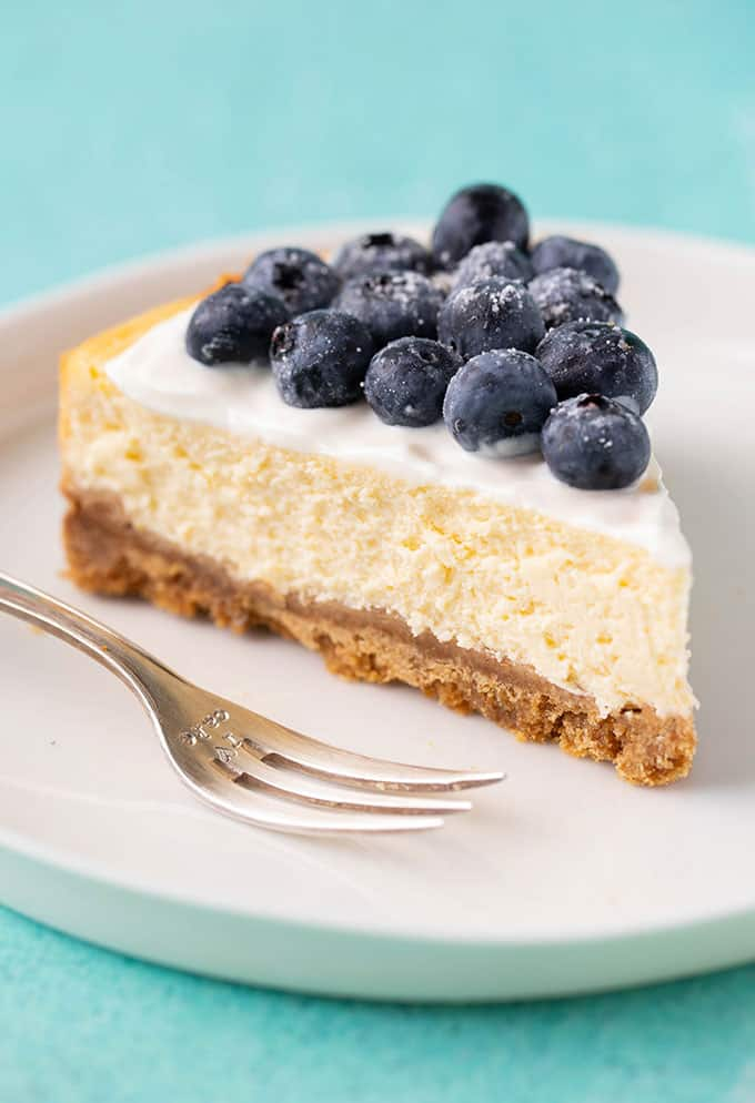 Top view of a slice of Lemon Cheesecake on a white plate