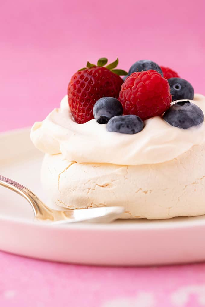 A mini pavlova topped with cream and berries on a white plate