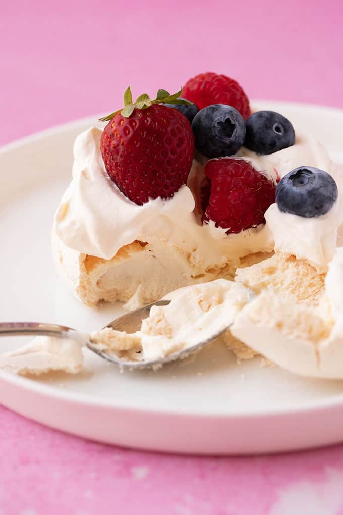 A spoon digging into a homemade Mini Pavlova