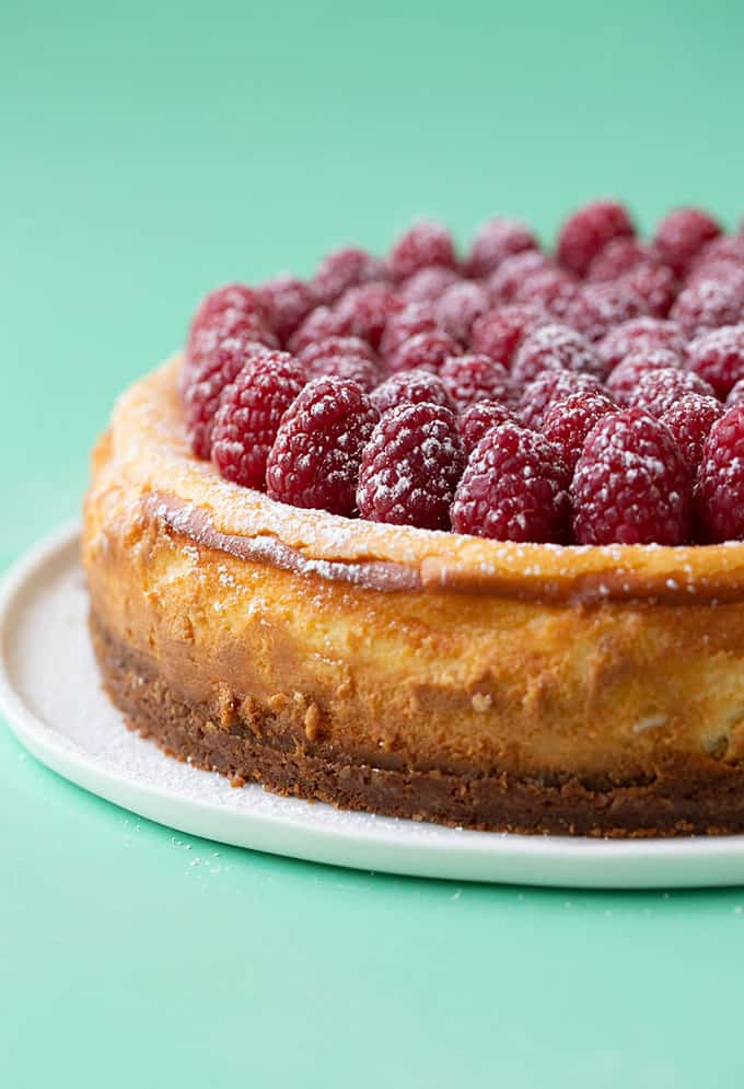 A Baked White Chocolate Cheesecake topped with fresh raspberries and icing sugar