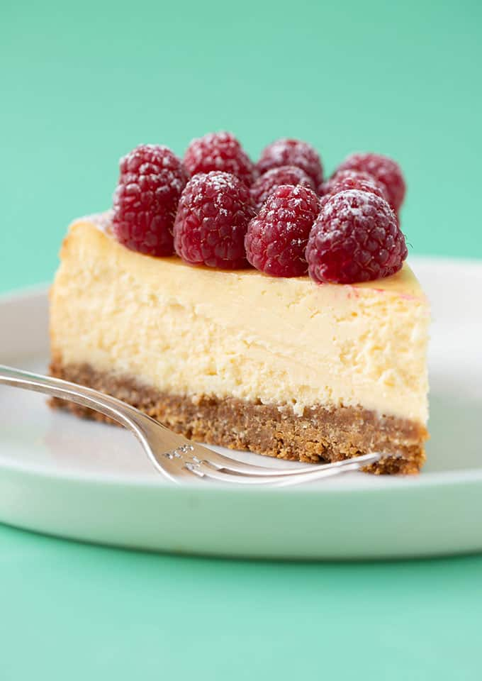 A slice of White Chocolate Raspberry Cheesecake on a white plate