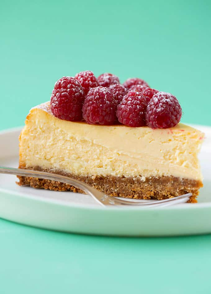 A slice of White Chocolate Cheesecake on a white plate with a fork