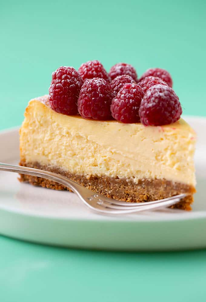 A beautiful slice of White Chocolate Cheesecake topped with fresh raspberries