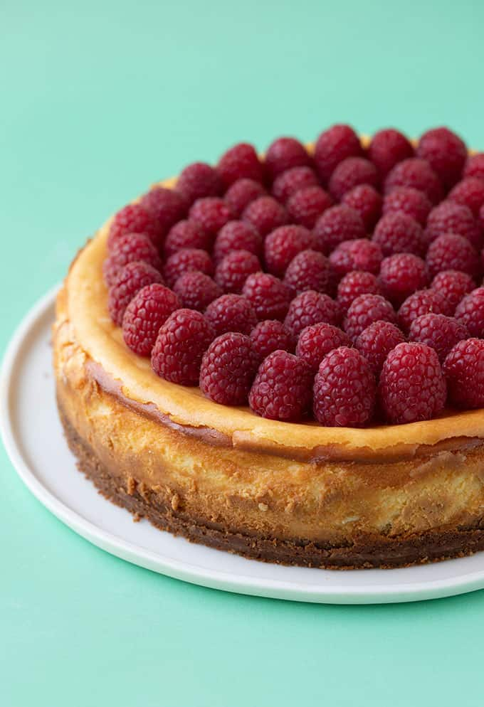 A whole baked White Chocolate Cheesecake topped with fresh raspberries