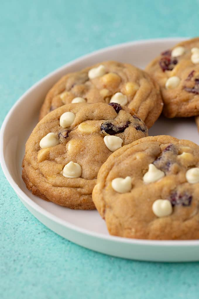 A plate of White Chocolate Cranberry Cookies on a turquoise background