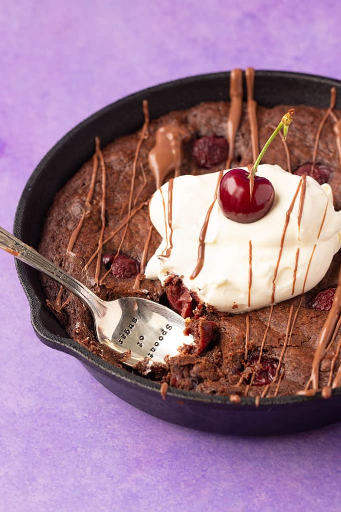 A Black Forest Skillet Brownie with a spoon digging into it