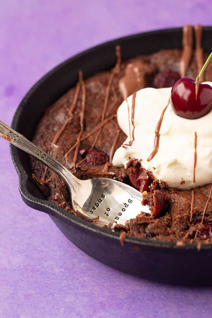 Digging into a Black Forest Skillet Brownie topped with whipped cream