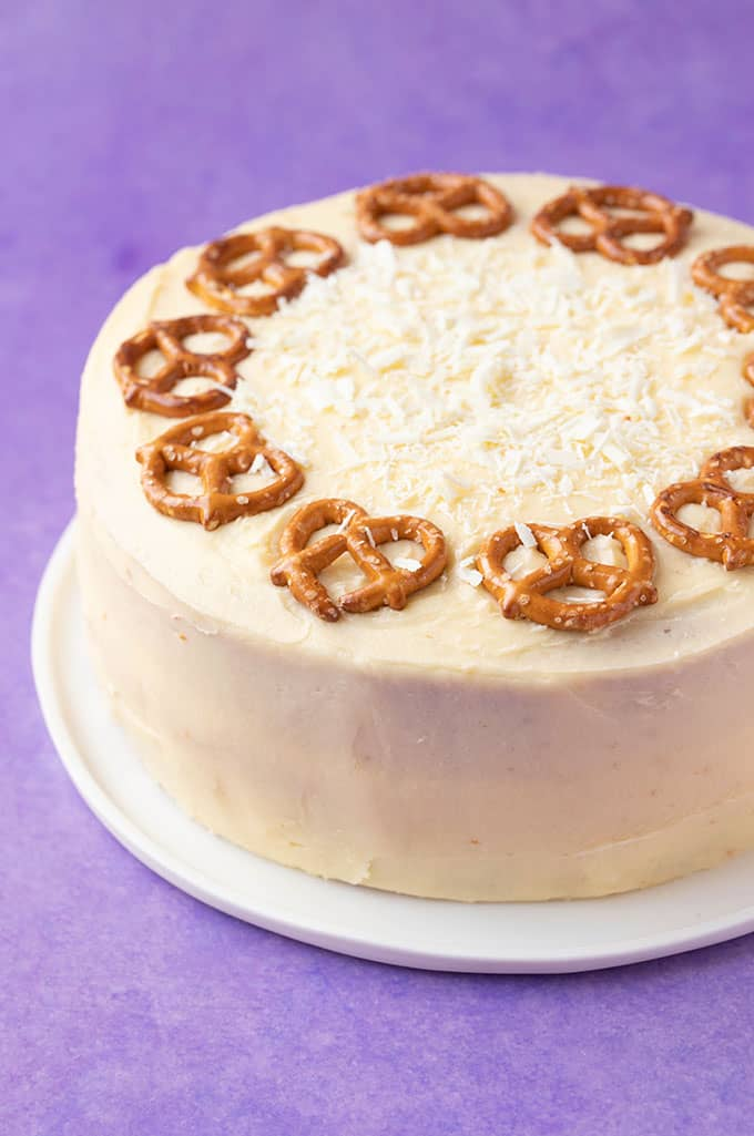 An Eggnog Cake decorated with pretzels on a purple background