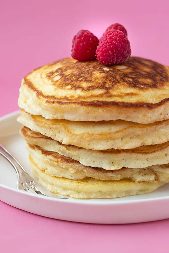 A stack of American Pancakes on a pink background