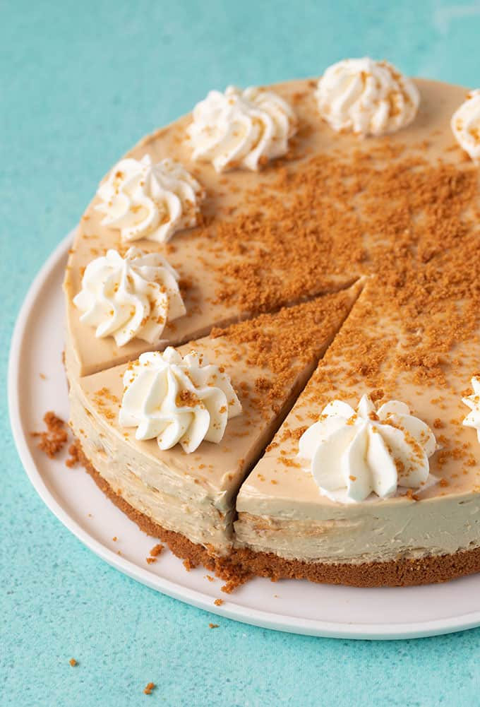 A homemade Biscoff Cheesecake decorated with swirls of whipped cream