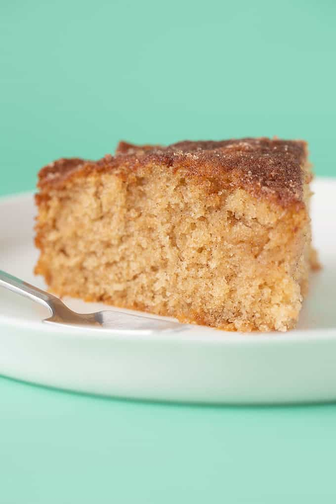 Close up of a slice of Cinnamon Cake with a green background