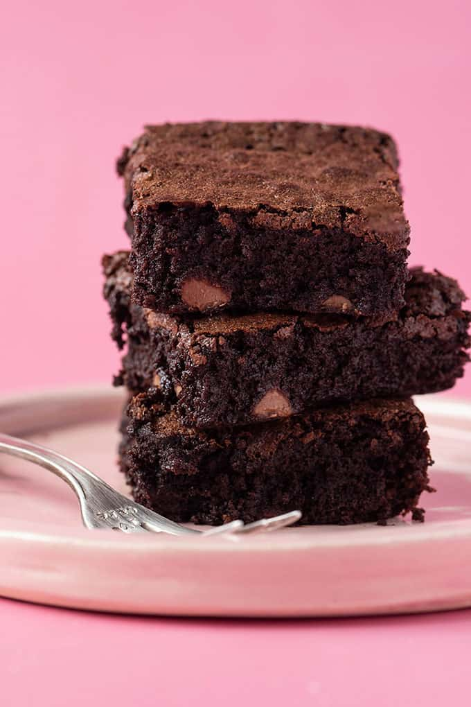 Homemade Flourless Brownies on a plate with a pink background