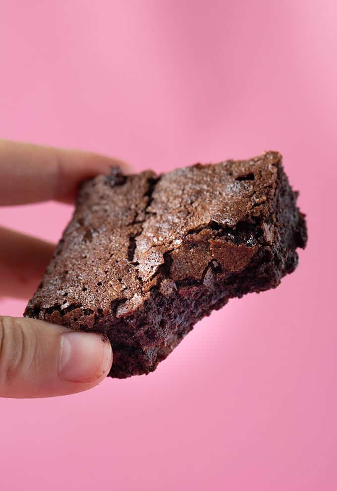A hand holding a homemade Flourless Brownie