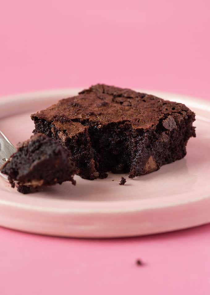 A half eaten Flourless Brownie on a pink background