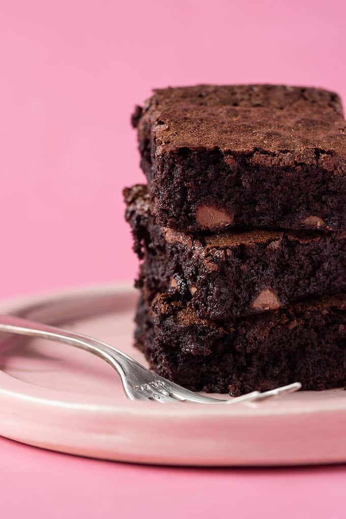 A stack of homemade Flourless Brownies on a pink plate