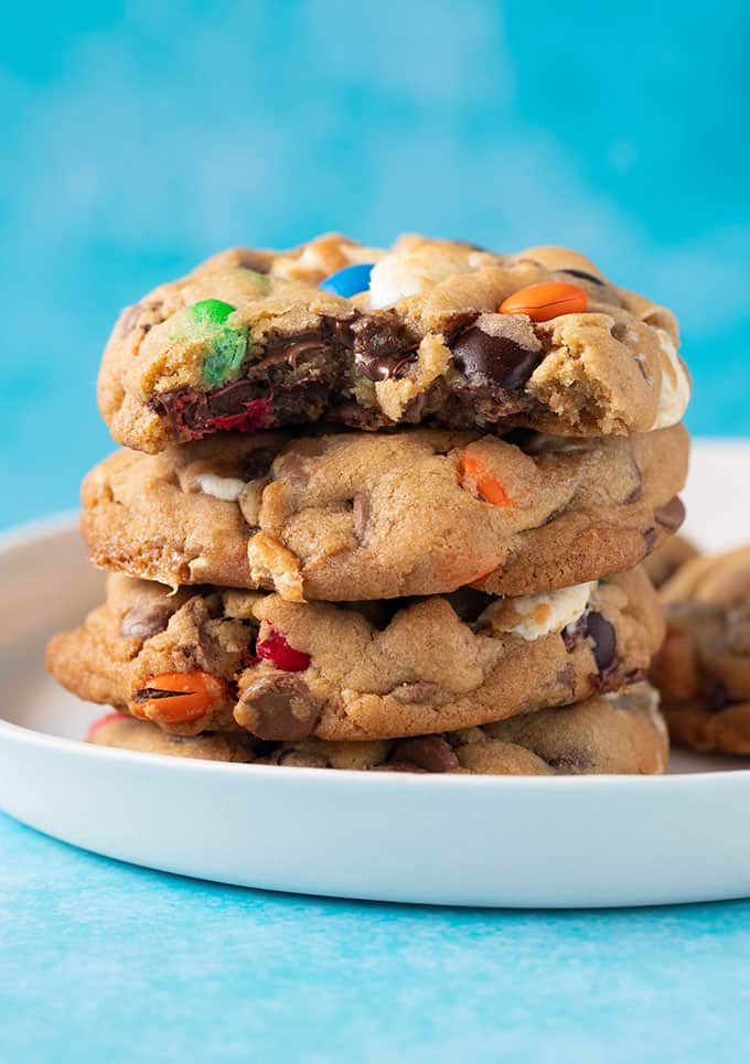 A stack of thick and chewy M&M Cookies on a blue background
