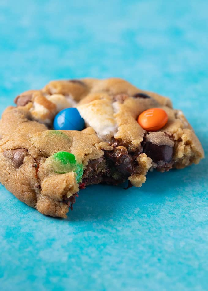 Close up of a homemade M&M Cookie with a bite taken out of it.