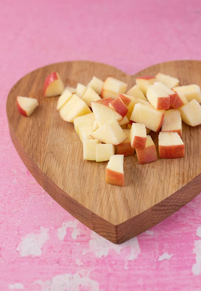 Pieces of chopped apple on a heart-shaped chopping board