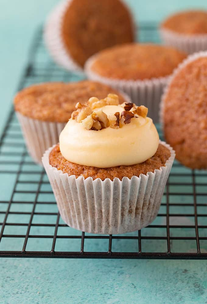 Close up of a Carrot Cake Cupcakes topping with cream cheese frosting and walnuts