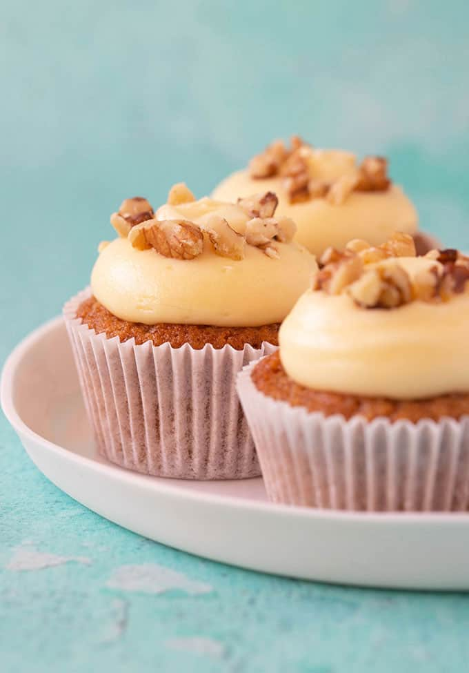 A plate of homemade Carrot Cake Cupcakes topped with walnuts