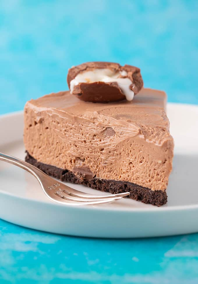 A big slice of Creme Egg Cheesecake sitting on a white plate