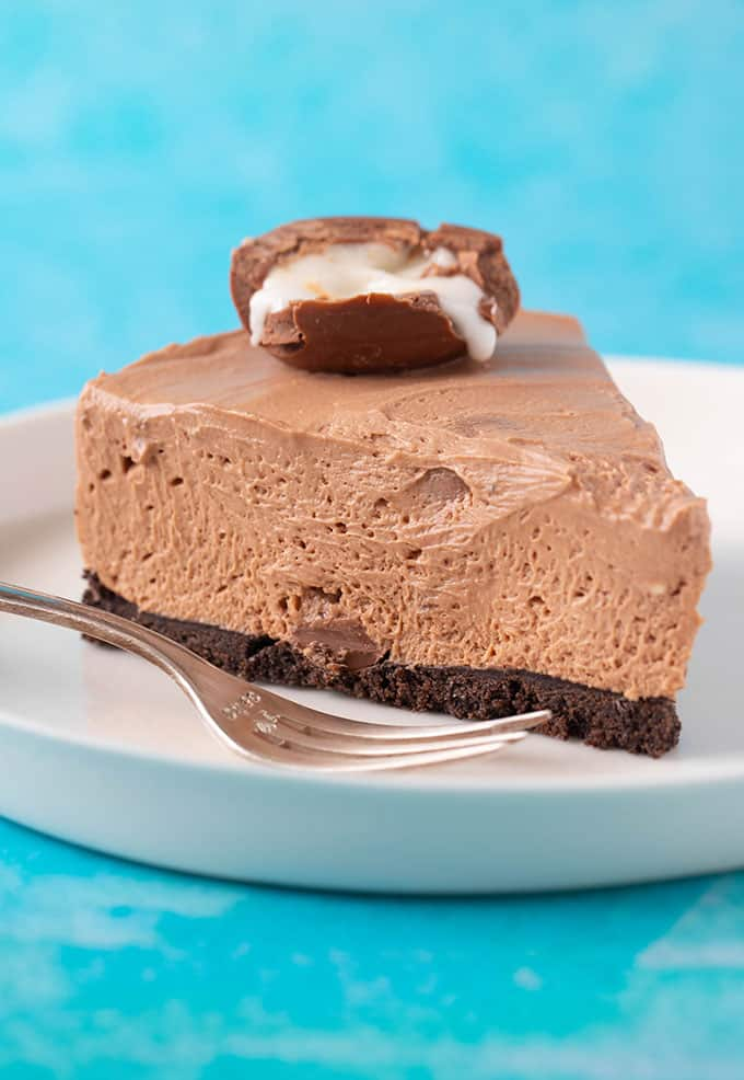 A slice of chocolate Creme Egg Cheesecake on a white plate