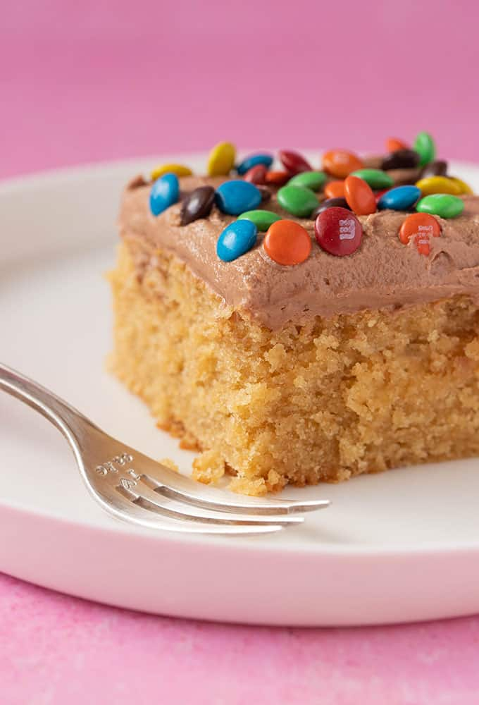 A piece of Peanut Butter Sheet Cake on a white plate