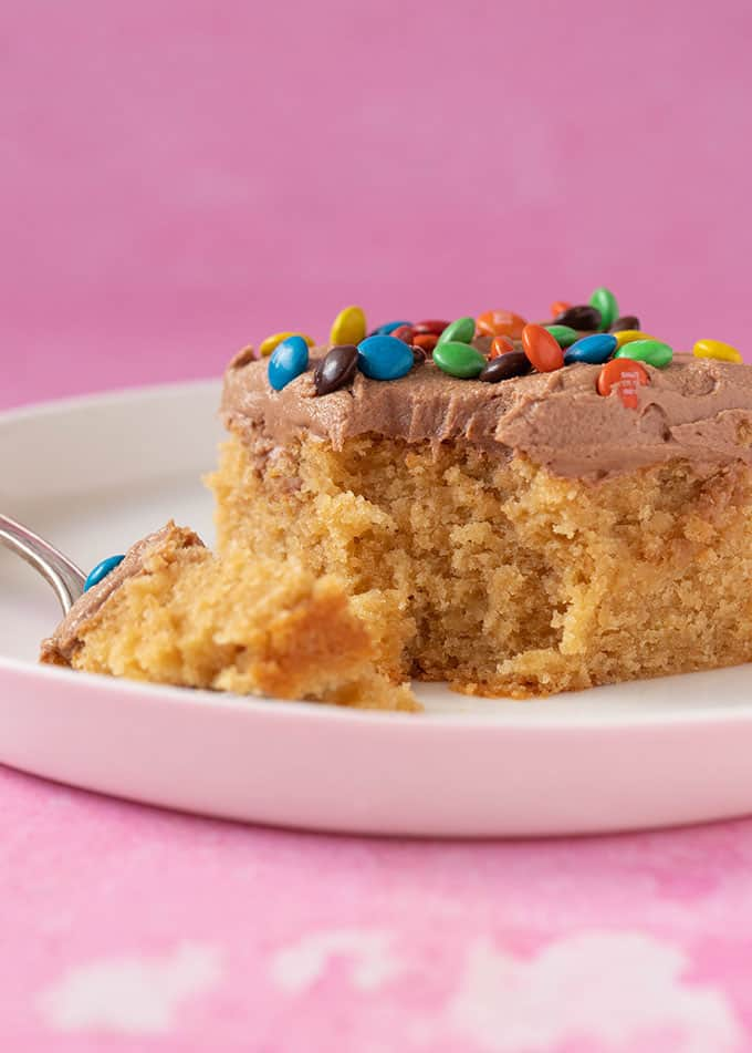 A piece of Peanut Butter Sheet Cake with a bite taken out of it