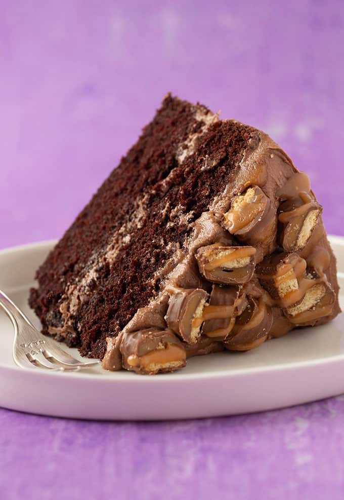 A big slice of Twix Cake covered in chopped Twix bars and caramel sauce