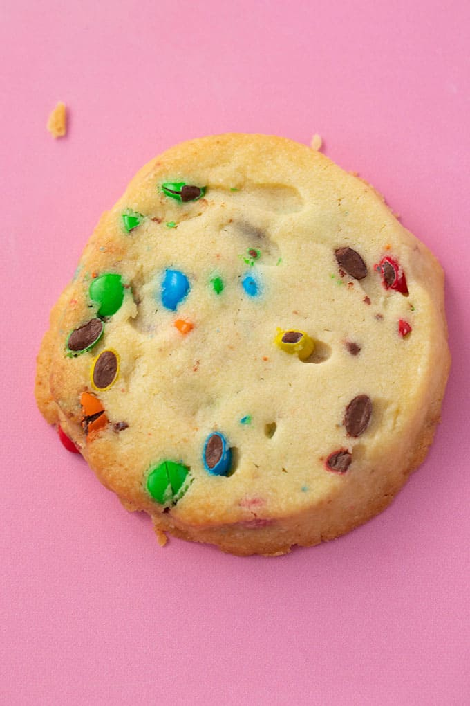 Close up of a homemade slice and bake cookie on a pink background