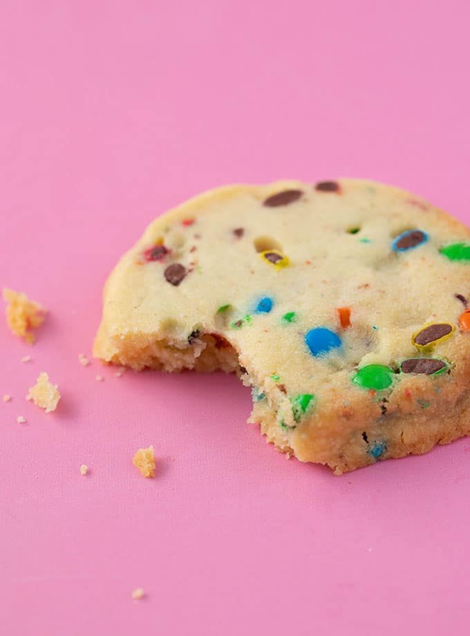 A homemade Shortbread Cookie filled with M&M's with a bite taken out of it