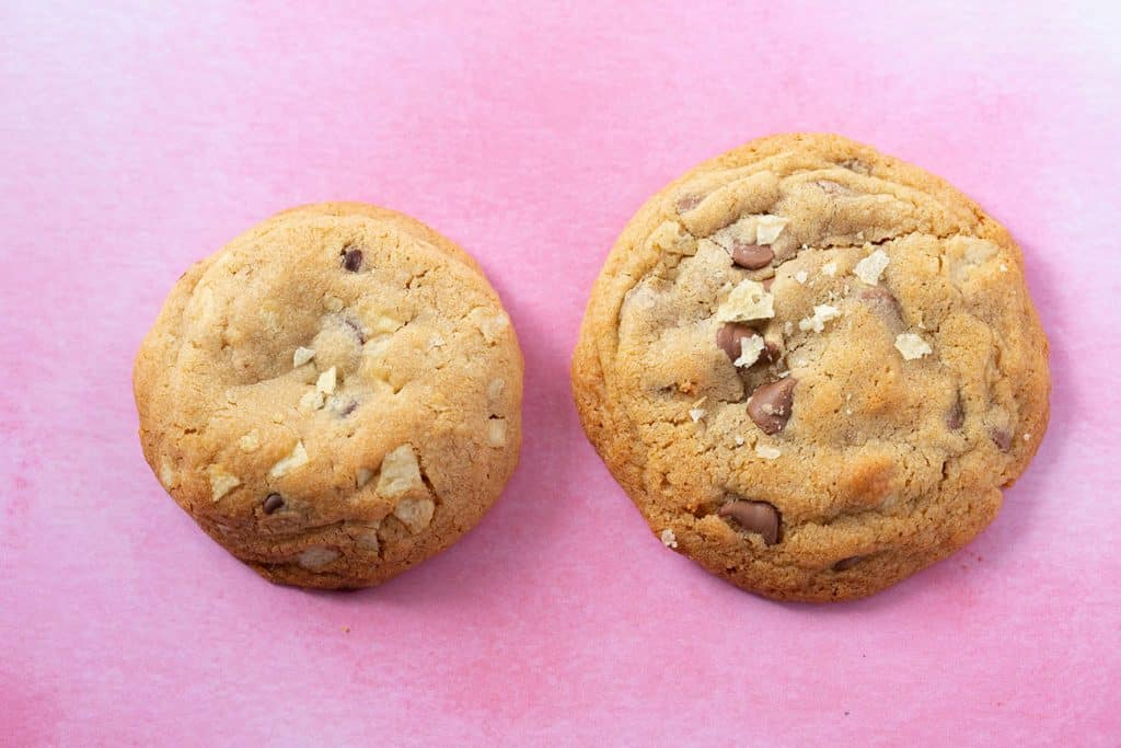 Two homemade chocolate chip cookies on a pink background