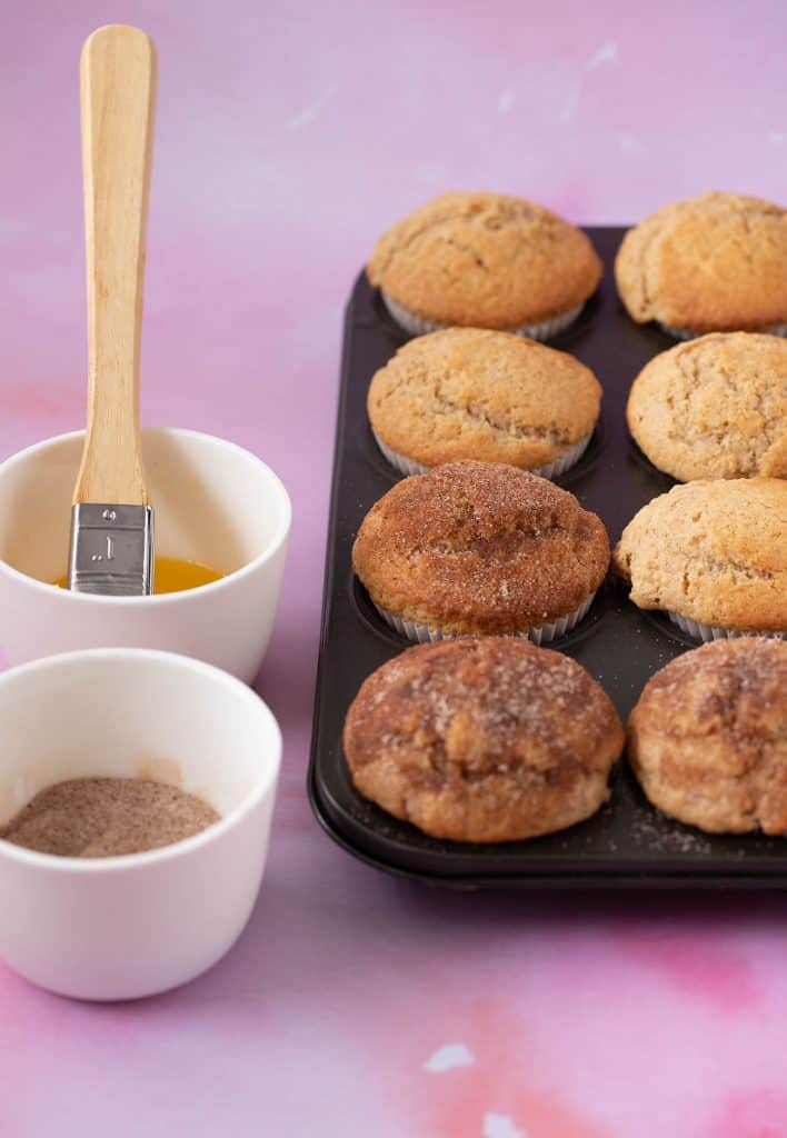 A batch of homemade Cinnamon Donut Muffins being brushed with melted butter and cinnamon sugar