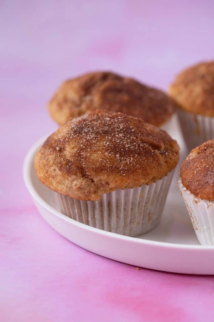 Close up of a plate of Cinnamon Sugar Muffins on a pink background