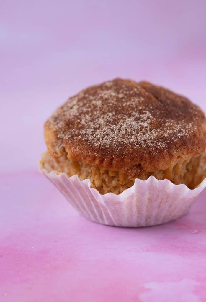 Close up of a homemade Cinnamon Donut Muffin with an unfolded cupcake liner