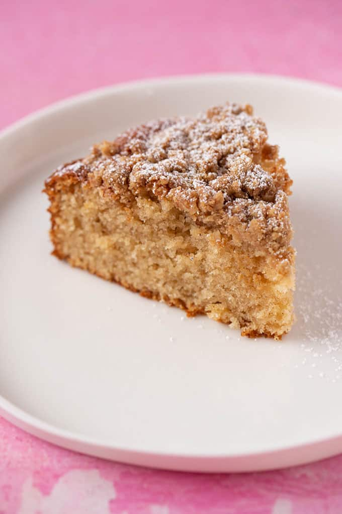 A slice of Coffee Cake dusted with icing sugar on a white plate