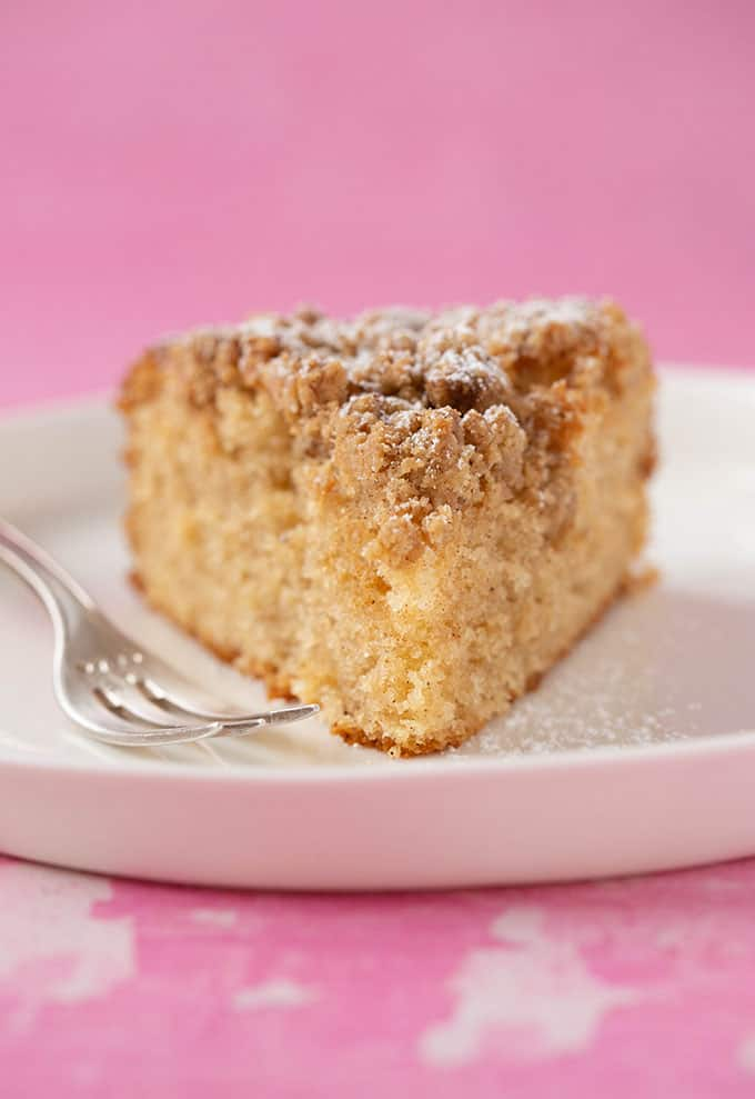 A slice of homemade Coffee Cake on a pink background