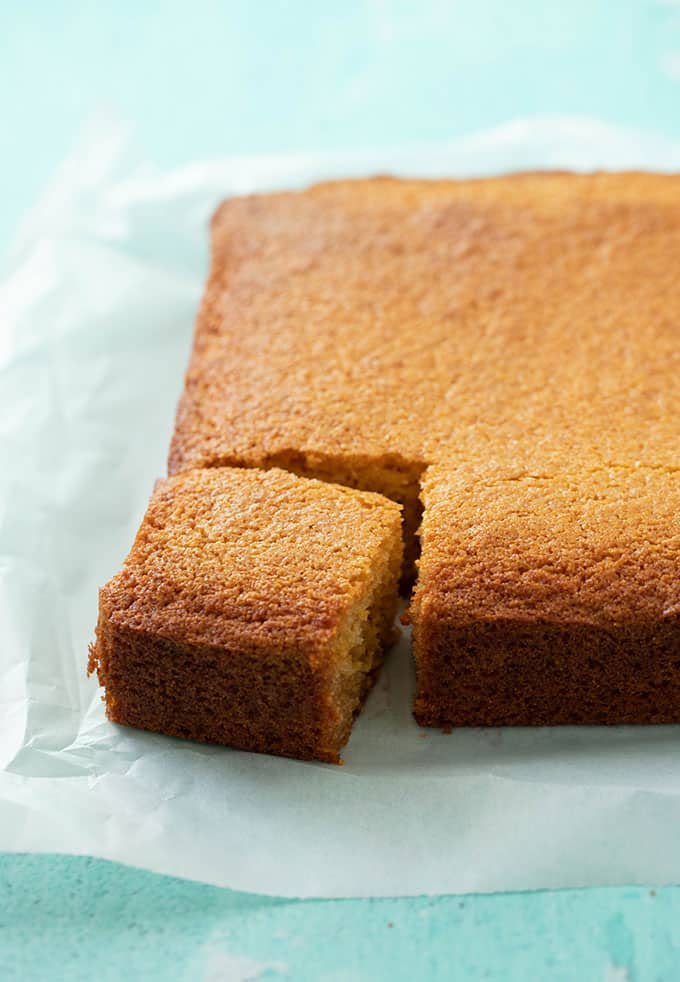 A piece of homemade Cornbread sitting on a piece of baking paper