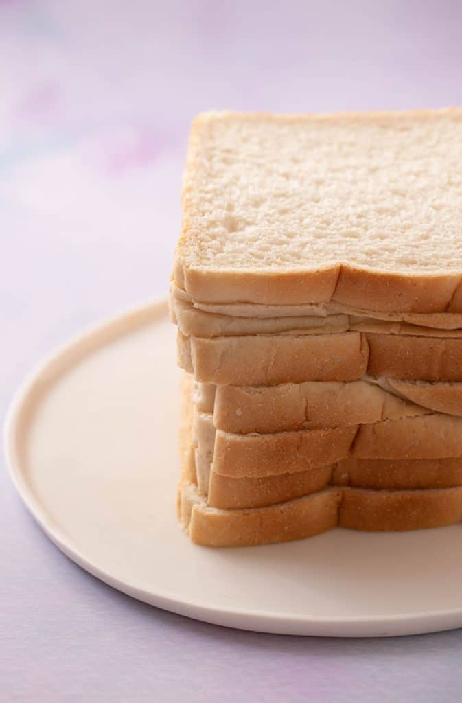 A stack of white bread on a white plate