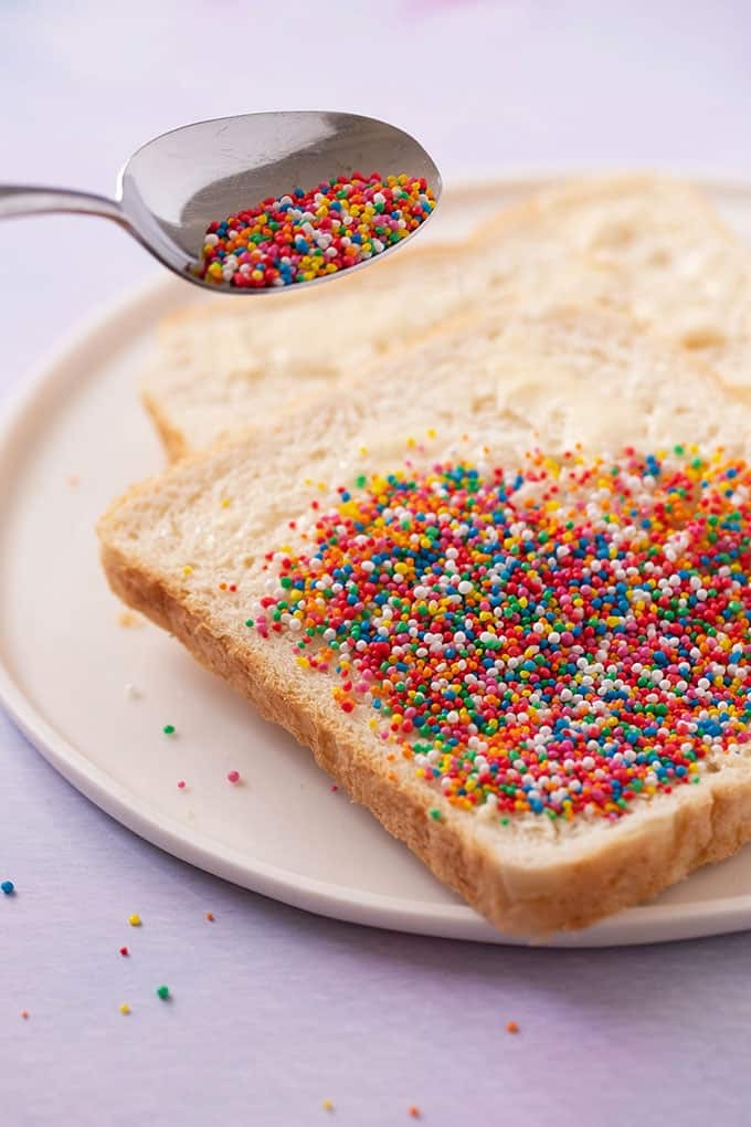 A piece of white bread covered in 100's & 1000's sprinkles