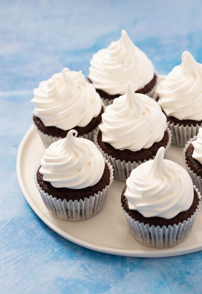 A plate of Chocolate Marshmallow Cupcakes on a blue background
