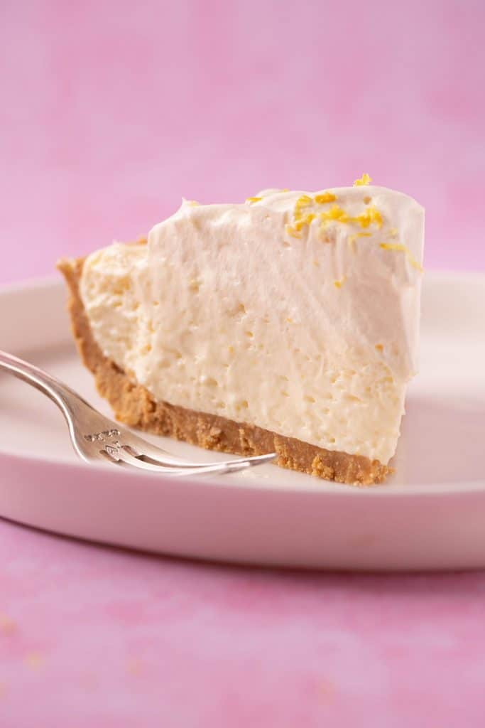 A slice of Lemon Pie topped with whipped cream on a white plate