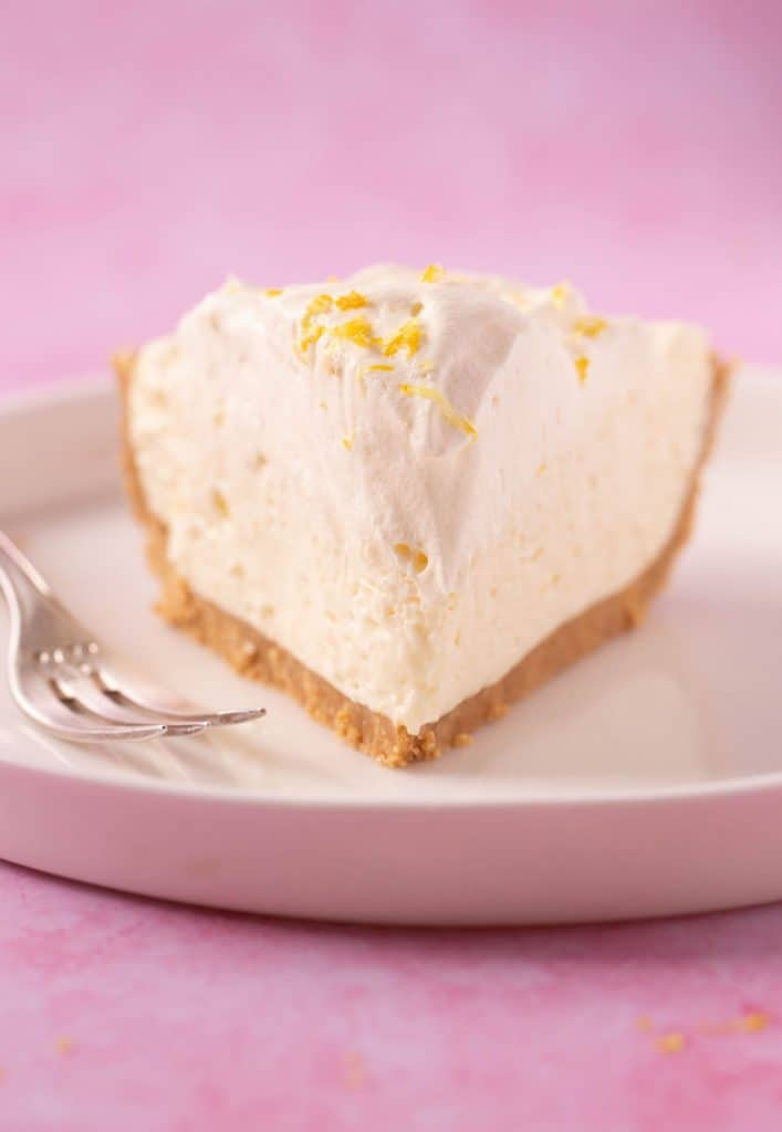 Close up view of a slice of Lemon Pie on a cake plate with a fork