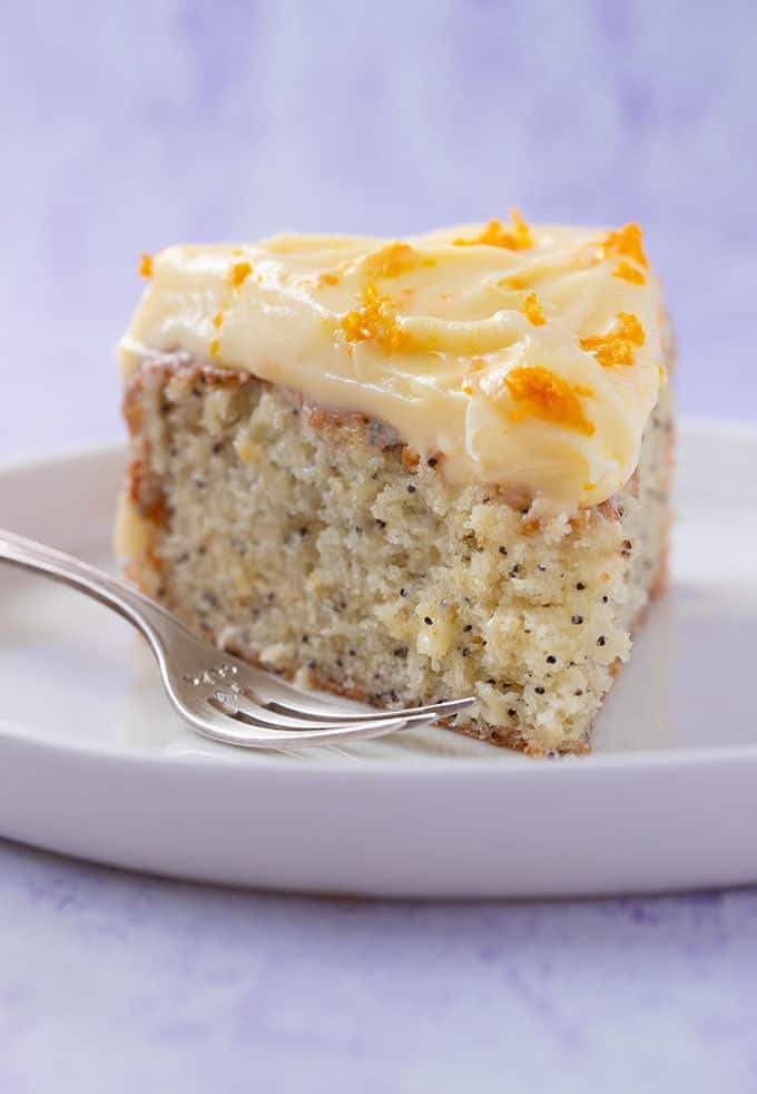 A big slice of Orange and Poppy Seed Cake on a white plate with a cake fork