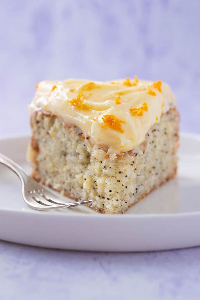 Close up of a slice of homemade Orange and Poppy Seed Cake with a purple background