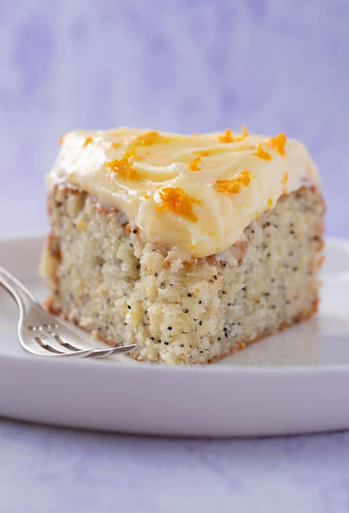 Front view of a slice of Orange and Poppy Seed Cake with sticky cream cheese frosting on a purple background