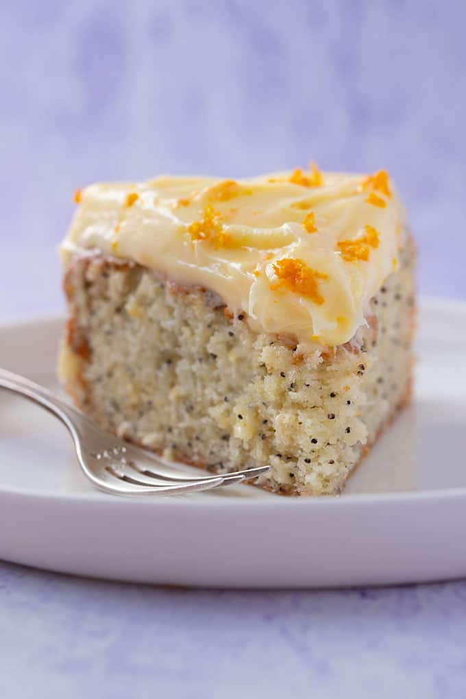 A slice of homemade Orange and Poppy Seed Cake on a white plate