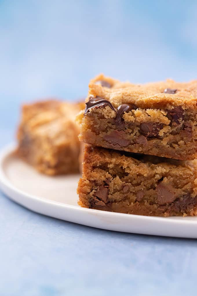Close up of a stack of Peanut Butter Chocolate Chip Blondies on a blue background