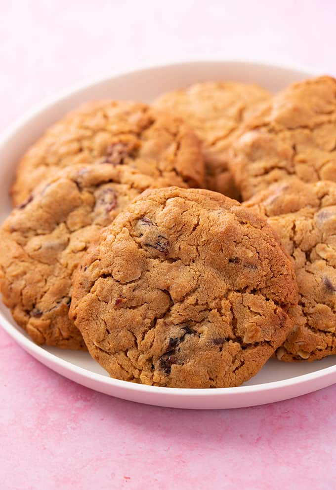 A white plate lined with homemade Peanut Butter Oatmeal Cookies on a pink background